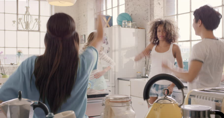 Young group of girl friends playful dancing in kitchen wearing pajamas tablet device playing happy music
