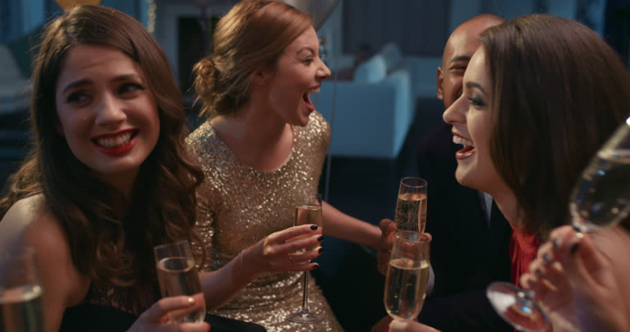 Friends holding up champagne flutes together in a toast at sexy glamorous party celebration cheers | Shutterstock HD Video #14076065