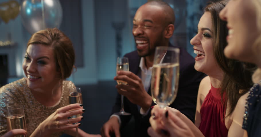 Friends holding up champagne flutes together in a toast at sexy glamorous party celebration cheers | Shutterstock HD Video #14076083