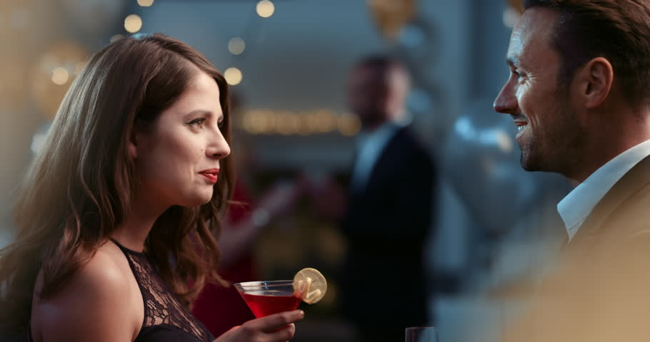 Sexy young couple meet flirting at glamorous party drinking champagne cocktail in love having fun together feeling attraction