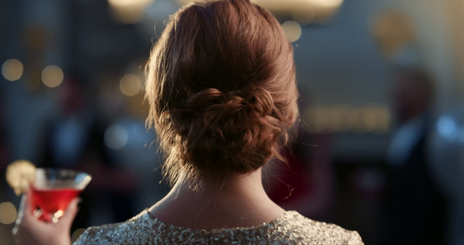 Back view of styled hair on elegant woman dressed in gold drinking red cocktail facing glamorous glitzy party lights