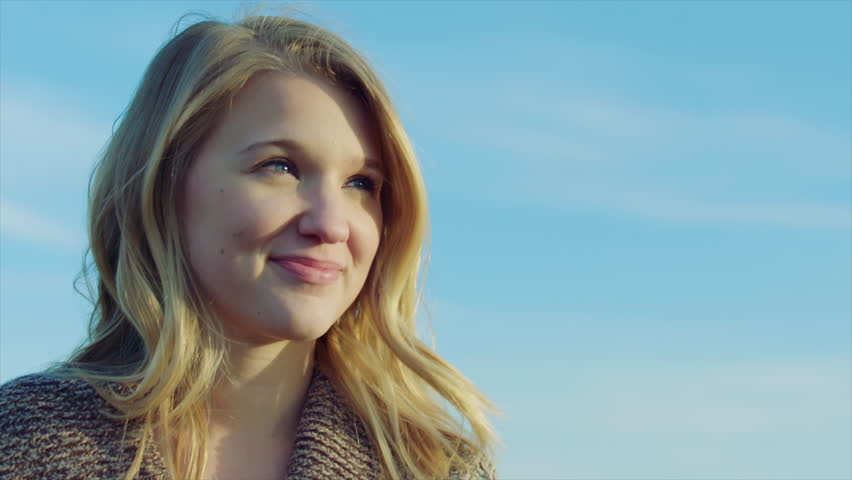Close up portrait of pretty young blonde girl looking up at sky, looks at camera and smiles   Shutterstock HD Video #14082980
