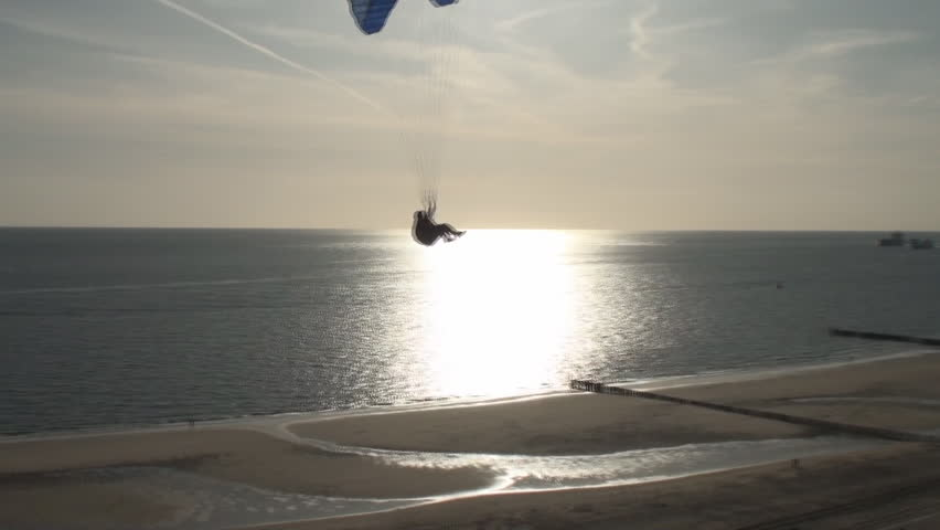 Parasailer sailing over the dunes and the beach along the coast of the province Zealand in the Netherlands when the sun sets.