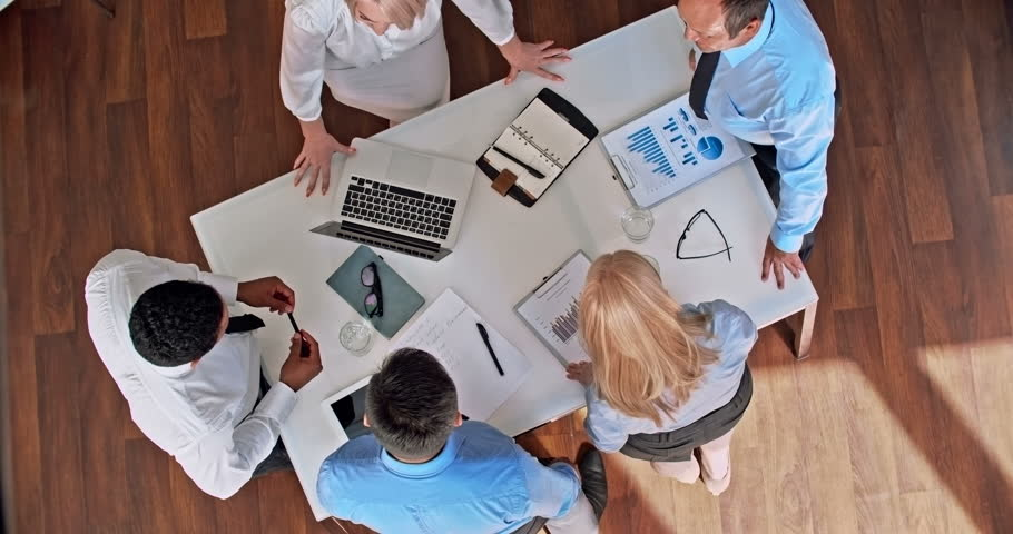 Directly above view of business professionals discussing financial report in the office | Shutterstock HD Video #14111615