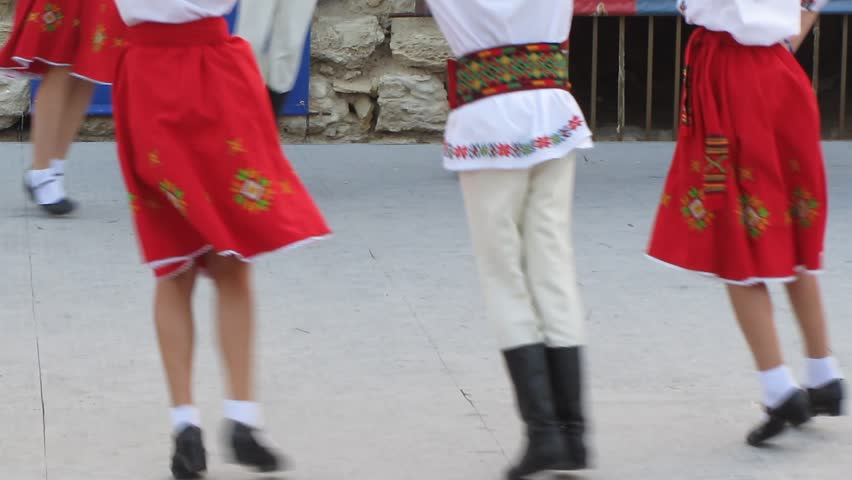 Young people in traditional ethnic clothing are dancing traditional East European dances.