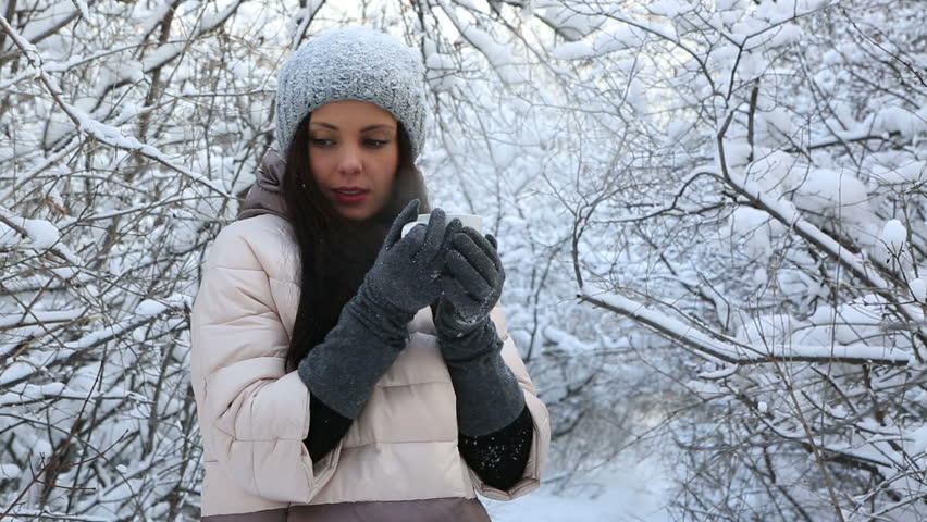 Beautiful happy girl warms up with hot tea. Snow covered trees in winter park. | Shutterstock HD Video #14117435