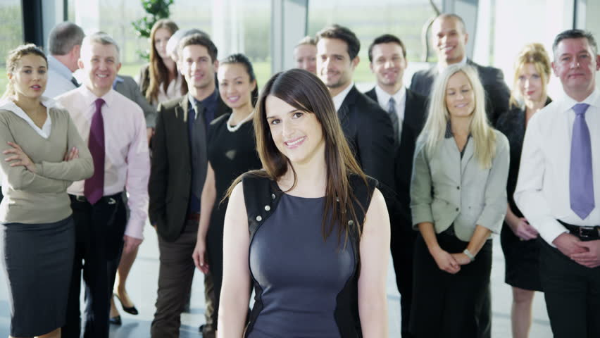 4k / Ultra HD version Portrait of a beautiful young businesswoman who is standing in front of the rest of her business team. They all look into the camera and smile. In slow motion. Shot on RED Epic | Shutterstock HD Video #14127446