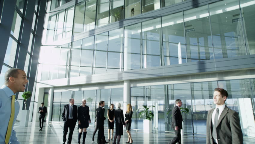4k / Ultra HD version Two confident and attractive young businessmen meet and shake hands in a busy modern office building. Other workers can be seen walking around the building. Shot on RED Epic | Shutterstock HD Video #14128136