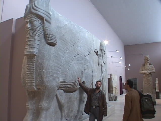 IRAQ - CIRCA 2003: An Iraqi man looks at a Mesopotamian relic in the Baghdad Museum circa 2003 in Iraq.