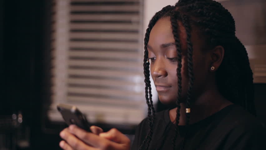 Black girl shocked and surprised at what she sees on her cell phone smartphone in the kitchen | Shutterstock HD Video #14150636
