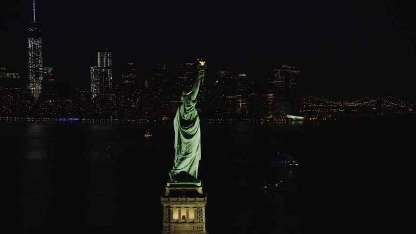 4k / Ultra HD version Helicopter aerial night view of Statue of Liberty, New York City State. Flying overhead. Her torch burns bright. Famous United States tourism attraction. Shot on RED Epic | Shutterstock HD Video #14164148