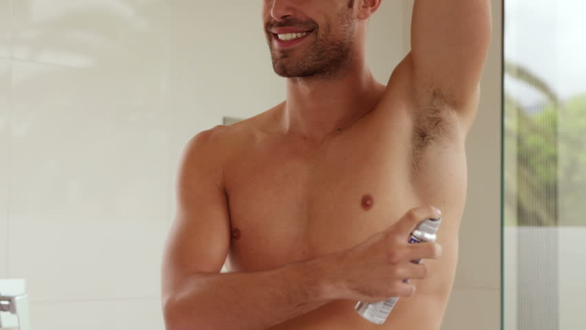 Handsome man putting deodorant on his armpit in the bathroom
