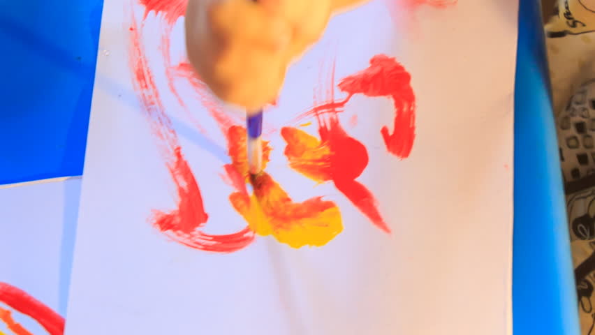 Kid's hand paints red and yellow wide lines and spots with brush on white paper sheet | Shutterstock HD Video #14183180