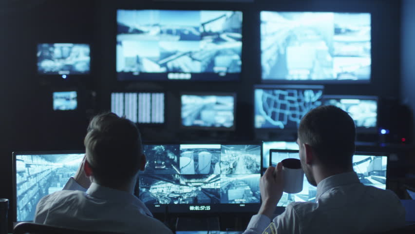 Two security officers noticed a trespasser on a surveillance computer screen in a dark monitoring room. Shot on RED Cinema Camera in 4K (UHD). | Shutterstock HD Video #14186711