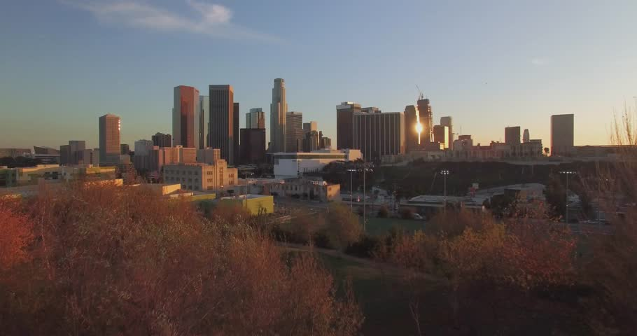 From The Bushes Into Downtown Los Angeles / Aerial 4K footage taking off from behind the trees and into downtown Los Angeles during sunset/sunrise with clear skies and minimal traffic.
