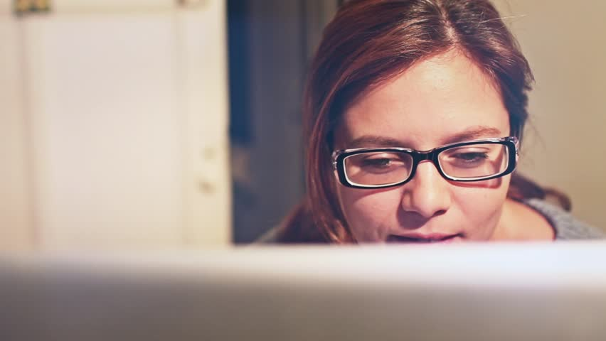 Woman with glasses on computer having fun - 1080p. Girl smiling and having fun using laptop at home - 1080p | Shutterstock HD Video #14262935