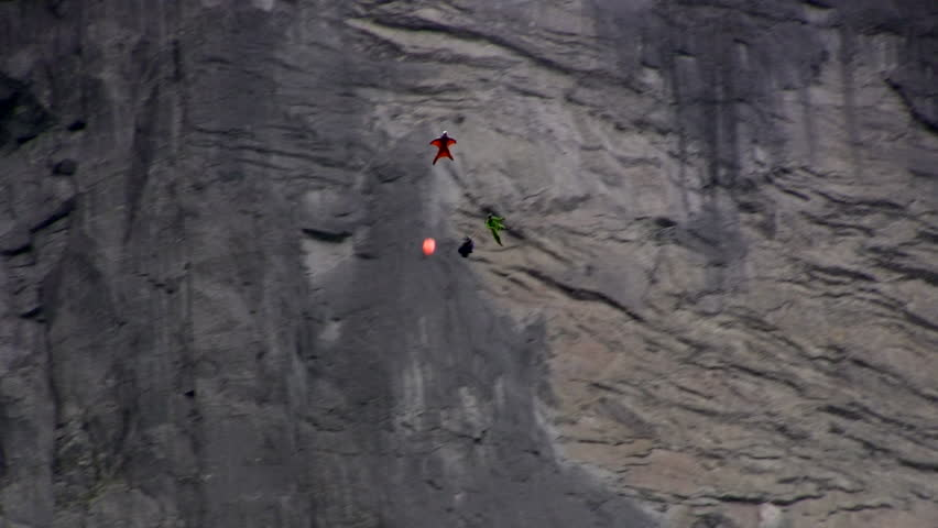Two base jumper jump one after the other from a big cliff in norway. Shot from under