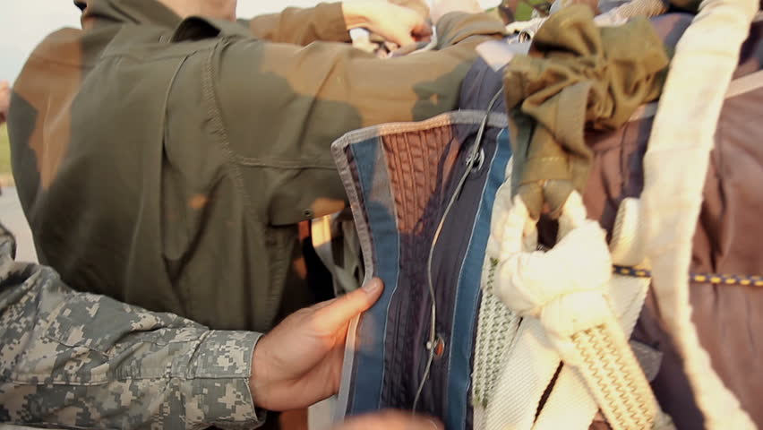 Closeup of military instructor checking paratroopers parachute