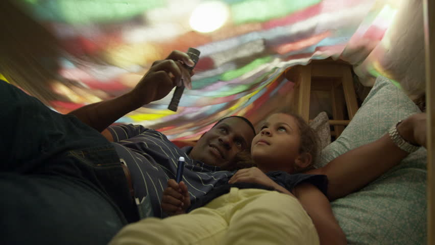 Father and daughter spending time together in a blanket fort playing with some flashlights.