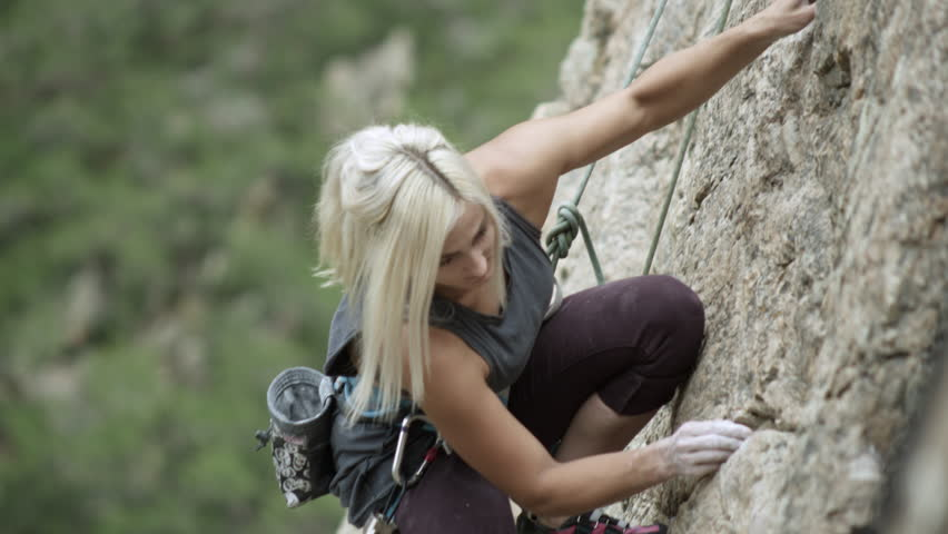 Woman rock climbing and topping out, personal goal setting achievement.