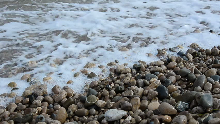 Sea surf. Waves runs on coastal pebble.