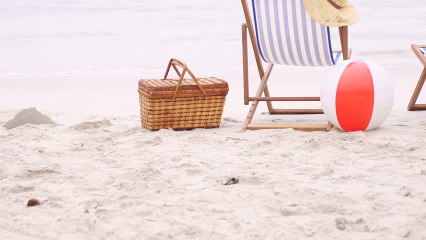 Deck chairs on the sand with towel, hat, ball and basket