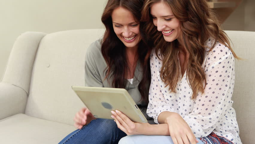 Happy brunettes using tablet on the sofa | Shutterstock HD Video #14290933