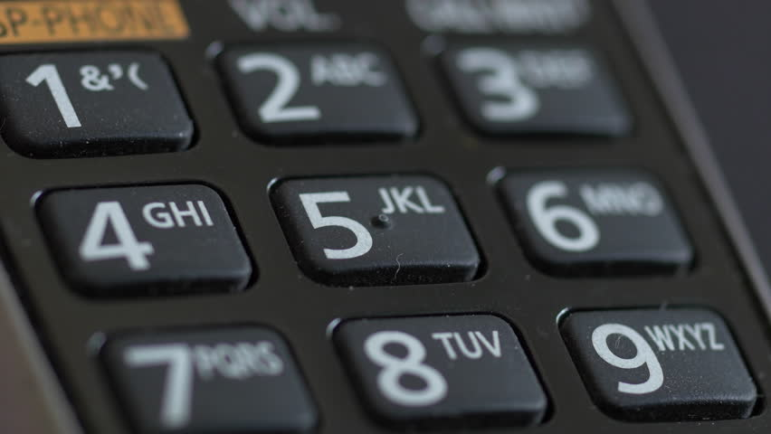 Extreme close up of a touch tone cordless phone keypad dialing 911 emergency call.