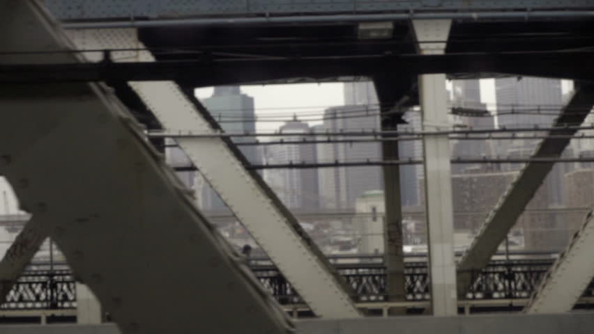 gritty shot of Lower Manhattan through bridge steel beams from moving subway train in NYC