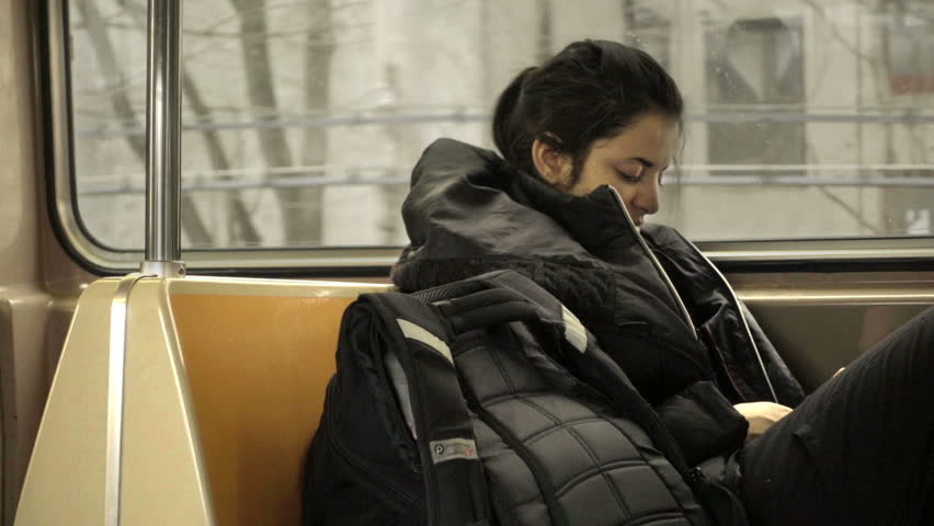 NEW YORK - JAN 25, 2015: sleeping passenger woman sitting on subway train riding through cold winter in Brooklyn NYC. The MTA provides public transportation throughout the five boroughs of the city. | Shutterstock HD Video #14304994