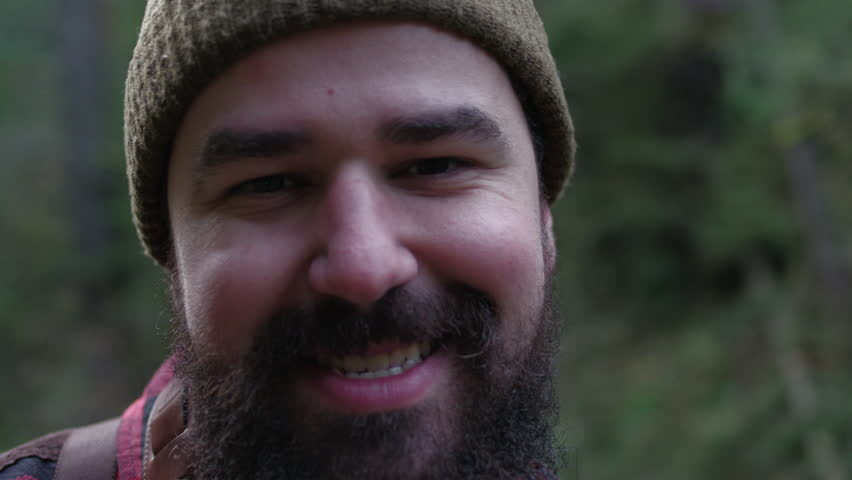 Portrait of a smiling lumberjack woodsman in flannel out in the forest.   Shutterstock HD Video #14310379