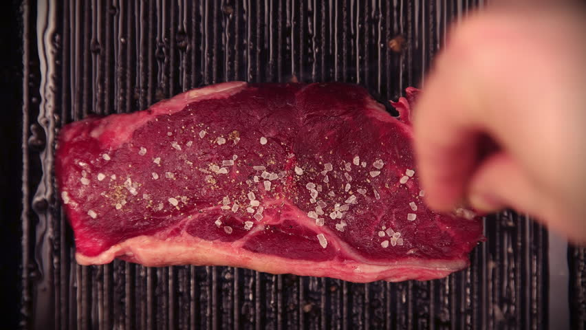 Delicious steak placed on hot grill garnished with salt and pepper