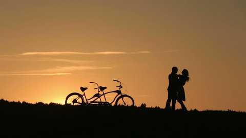 Romantic Couple with Tandem Bicycles Kissing While Sunset. Summer Nature Background with Beautiful Clouds in the Sky Close Up