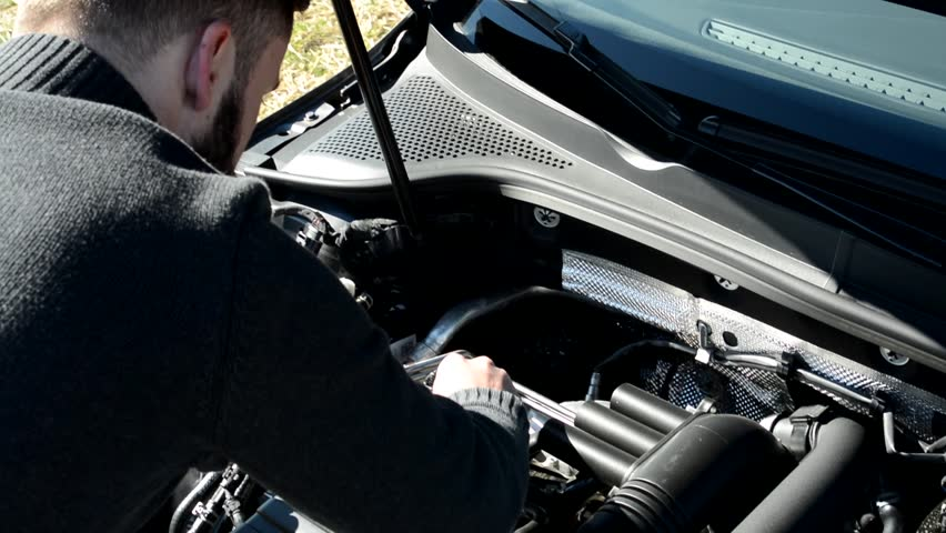handsome young hipster man looks on engine in car - accident on the road in countryside - over shoulder closeup #14349139