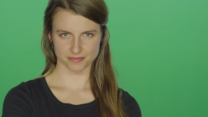 Young woman crosses her arms and glares, on a green screen studio background | Shutterstock HD Video #14361295