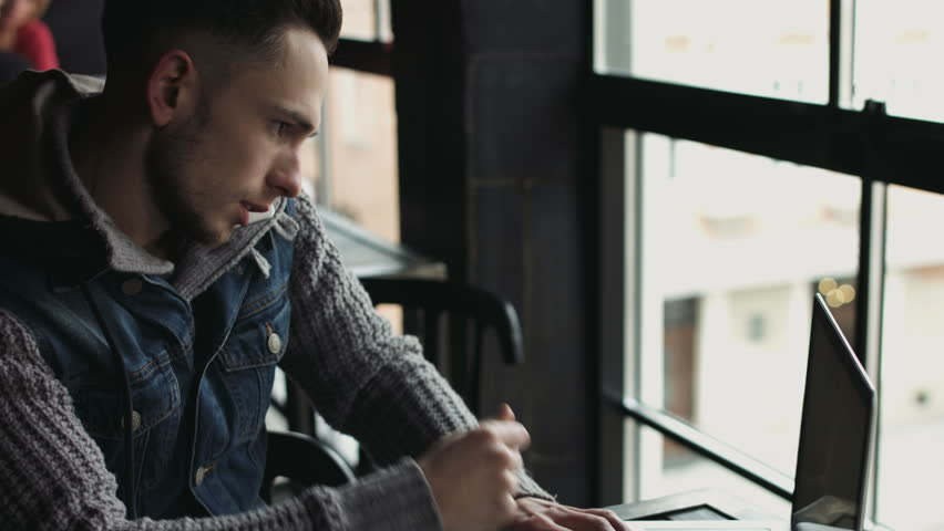 Male in his 20s working at the cafe. Attractive guy multitasking man talking on cellphone and typing on his laptop.  | Shutterstock HD Video #14369275