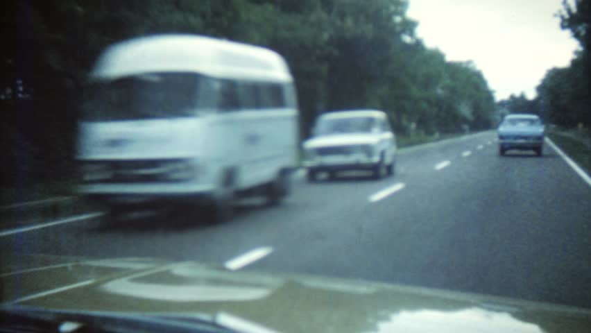 CIRCA 1968: Vintage 8mm film of a highway with old cars driving around