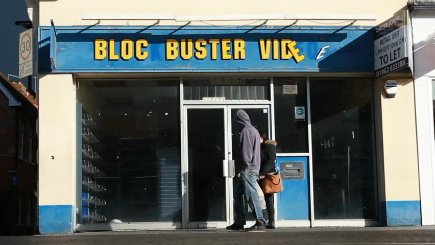 Pedestrians pass bankrupt Blockbuster video store wide. Newbury UK. Feb 2014