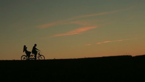 Silhouette of  Beautiful Couple Riding The Tandem Bicycles While Sunset. Summer Nature Background with Beautiful Clouds in the Sky Close Up.