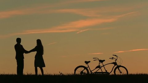 Romantic Couple with Tandem Bicycles Softly Kissing And Dancing  While Sunset. Summer Nature Background with Beautiful Clouds in the Sky Close Up