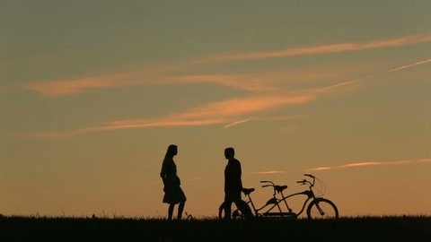 Fabulous Couple With Tandem Bicycles Dancing Waltz. Fantastic Sunset. Summer Nature Background