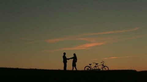 Romantic Couple with Tandem Bicycle Softly Kissing While Sunset. Summer Nature Background with Beautiful Clouds in the Sky Close Up
