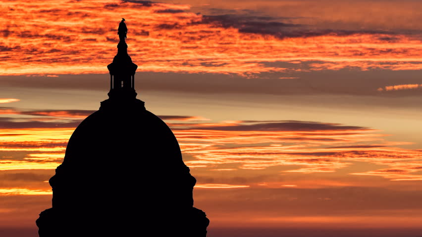 United States Capitol dome with sunrise time lapse sky.