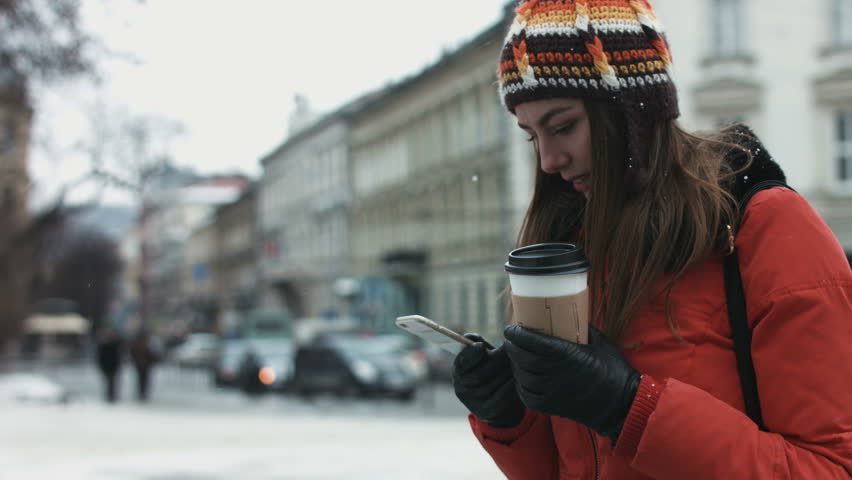 Young female being waiting for her friends outdoors and using smartphone to text. Girl is receiving a message on her mobile device. #14393161