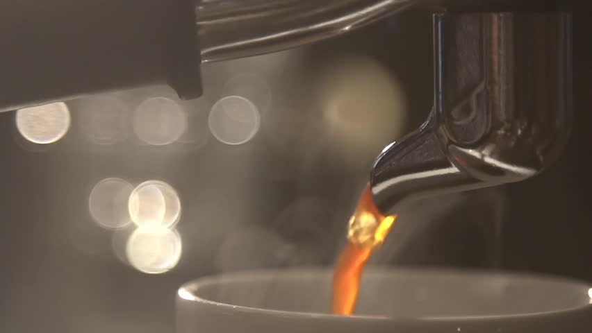 Coffee flows from cofee machine in slow motion