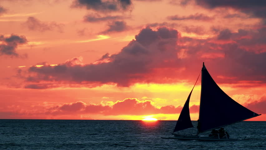 Amazing colors of tropical sunset. Sail boats silhouettes floating on ocean horizon. Boracay island, Philippines summer vacation