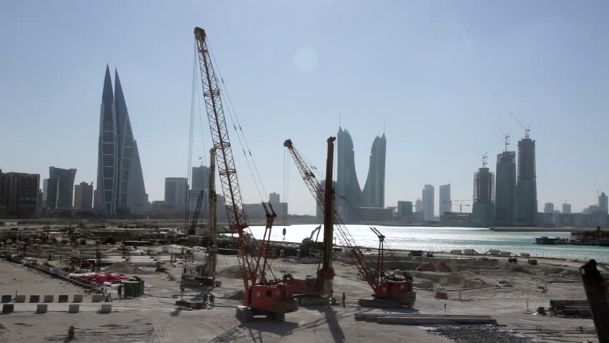 Construction Site in Bahrain with City Skyline on background. Cranes, vehicles and workers in movement, a very common scenario in Middle East. #14395969