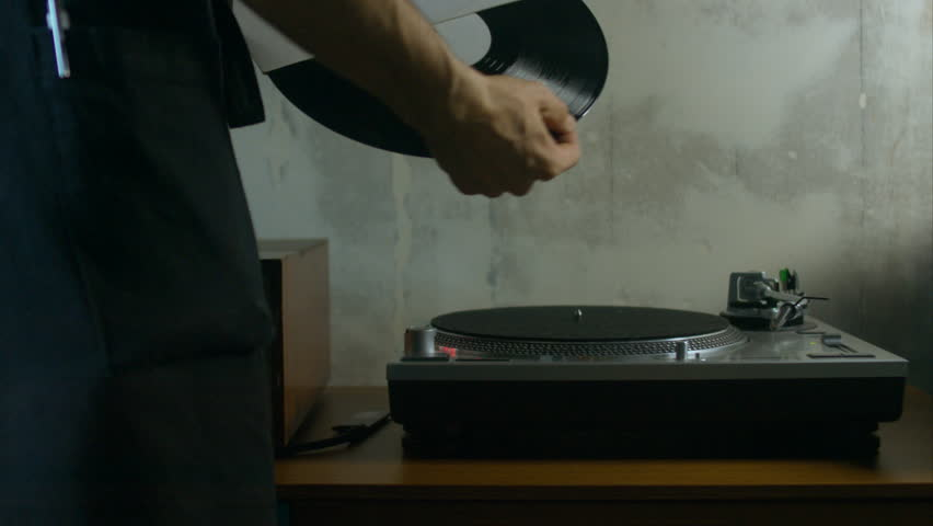 60 FPS close up shot of young adult attractive Caucasian bartender playing vinyl record on a vintage record player. Shot with Blackmagic URSA Mini #14400496