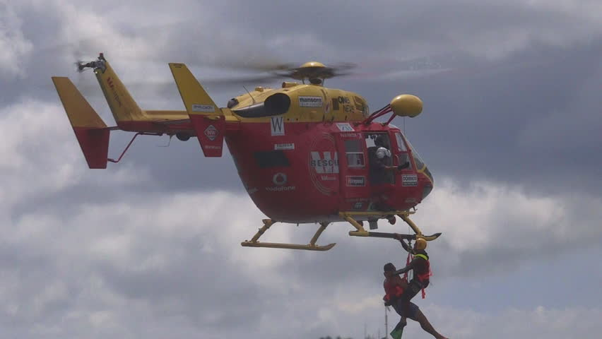 AUCKLAND,  NZL - JAN 30 2016:Westpac Rescue Helicopter crew in rescue mission.The crew are trained and equipped to operate day and night to medical transfers medevacs to rescue searches and airlifts.