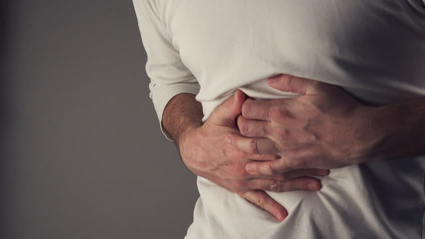 Bellyache, severe abdominal pain, man holding his belly and having painful cramps.